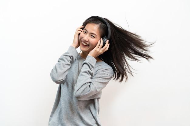 Heureuse jeune fille asiatique écoute de la musique de casque isolé sur fond blanc. Photo Premium