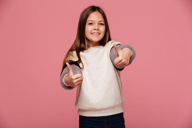 Heureuse Jeune Fille Brune Montrant Les Pouces Vers Le Haut Et Souriant Photo gratuit