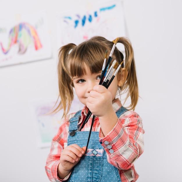 Heureuse jeune fille debout avec des pinceaux dans les mains Photo gratuit