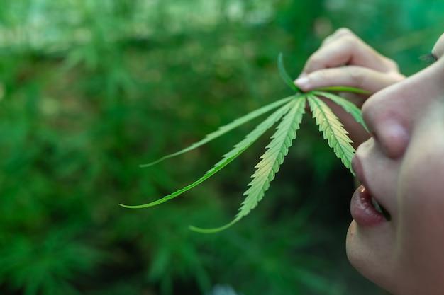 Heureuse jeune fille debout et tenant un cannabis. Photo gratuit