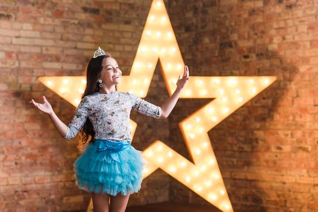 Heureuse jeune fille jouant devant une étoile brillante contre le mur de briques Photo gratuit