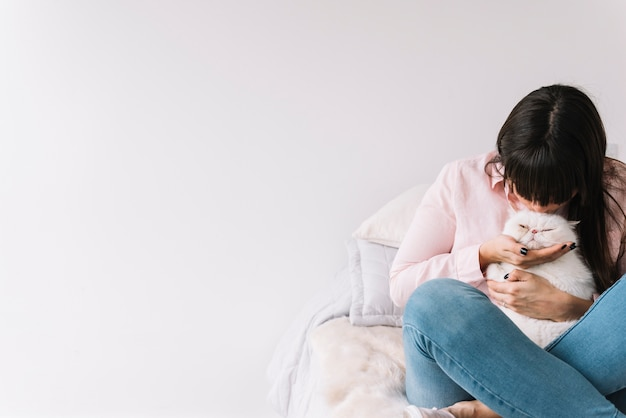 Heureuse jeune fille posant avec son chat Photo gratuit