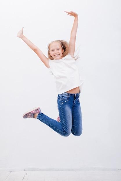 Heureuse Jeune Fille Sautant Par-dessus Un Fond Blanc Photo gratuit