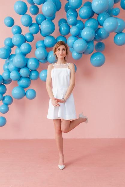 Heureuse jeune fille souriante en jolie robe blanche dansant sur fond rose. Photo gratuit