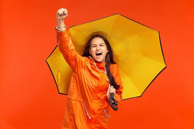 Heureuse Jeune Fille Souriante Posant Au Studio En Veste Orange Automne Isolé Sur Rouge. émotions Positives Humaines. Concept Du Temps Froid. Concepts De Mode Féminine Photo gratuit