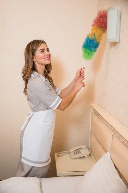 Heureuse jeune fille en uniforme nettoyer l'applique murale avec un plumeau Photo gratuit