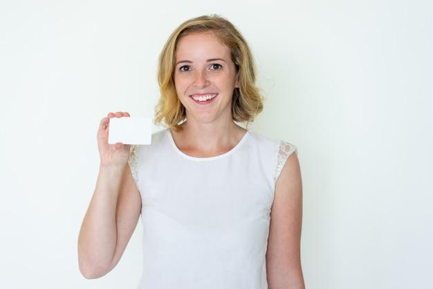 Heureuse jeune et jolie femme montrant une carte de visite vierge Photo gratuit