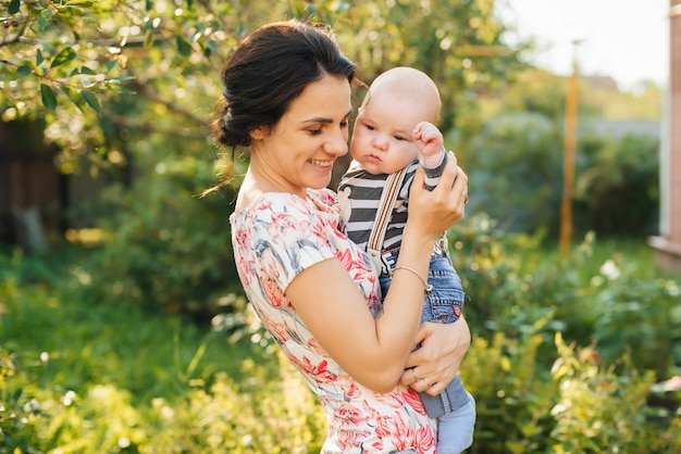 Heureuse jeune maman caucasienne avec un fils nouveau-né garçon dans les mains en souriant Photo Premium