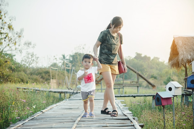 Heureuse jeune maman joue et s'amuse avec son petit bébé dans le parc par une journée d'été ensoleillée Photo gratuit