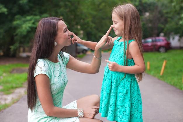 Heureuse jeune maman et sa fille s'amuser en plein air Photo Premium