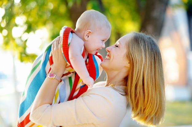 Heureuse jeune maman avec son petit bébé au coucher du soleil Photo Premium