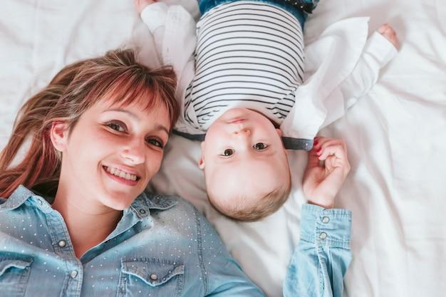 Heureuse jeune maman et son petit garçon allongé sur le lit et souriant Photo Premium