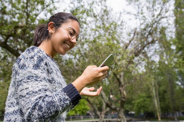 Heureuse jolie femme à l'aide de smartphone dans le parc Photo gratuit
