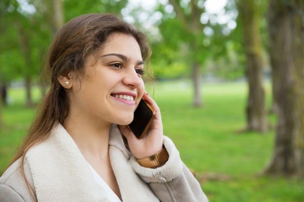 Heureuse jolie femme appelant sur un smartphone dans le parc Photo gratuit