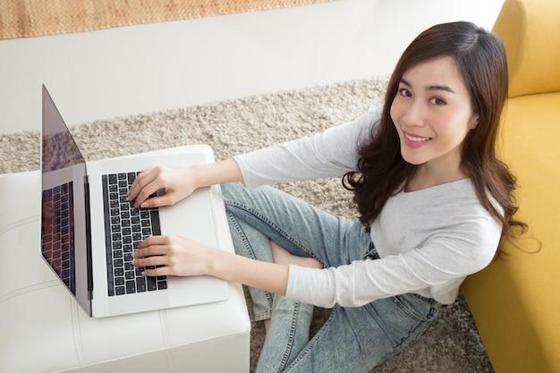 Heureuse jolie femme asiatique à l'aide d'un ordinateur portable assis sur le sol dans le salon Photo Premium