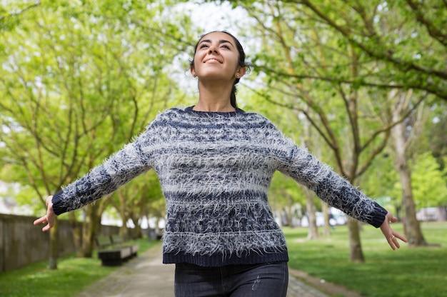 Heureuse jolie femme répandre les mains et marcher dans le parc Photo gratuit
