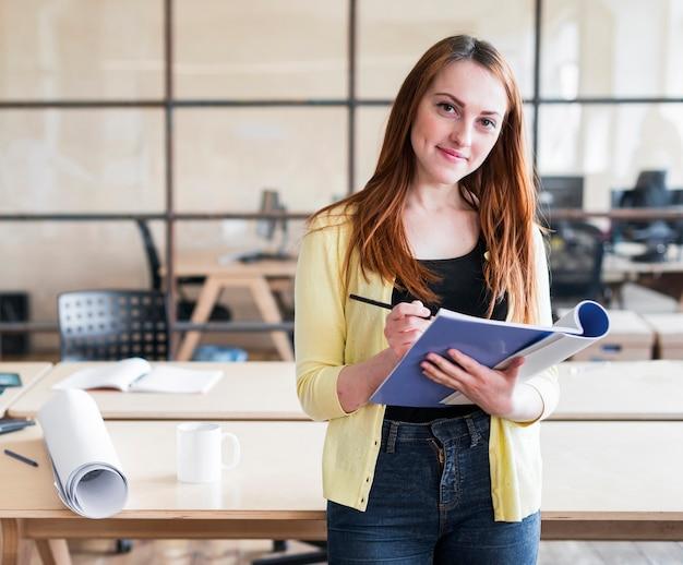 Heureuse jolie femme se penchant sur le bureau, tenant un livre et un crayon sur le lieu de travail Photo gratuit