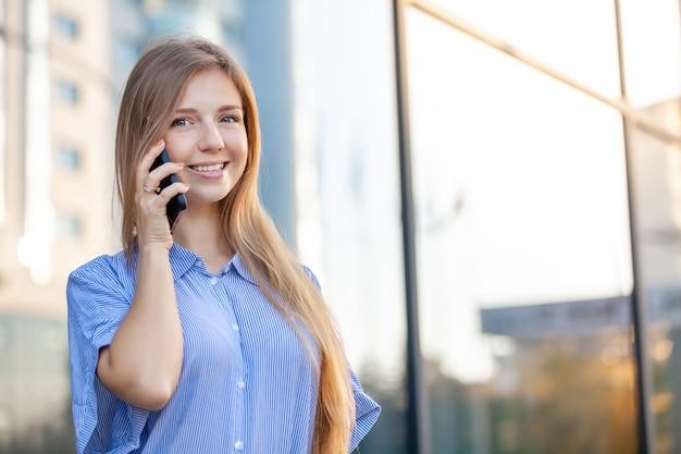 Heureuse Jolie Femme Séduisante Parlant Au Téléphone En Face Du Bureau Photo Premium