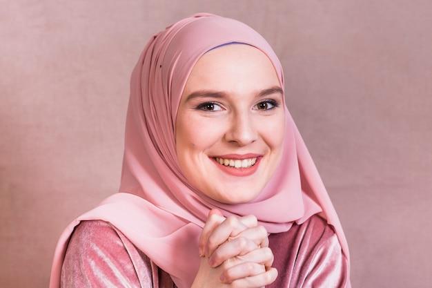 Heureuse jolie femme avec ses mains jointes sur fond coloré Photo gratuit