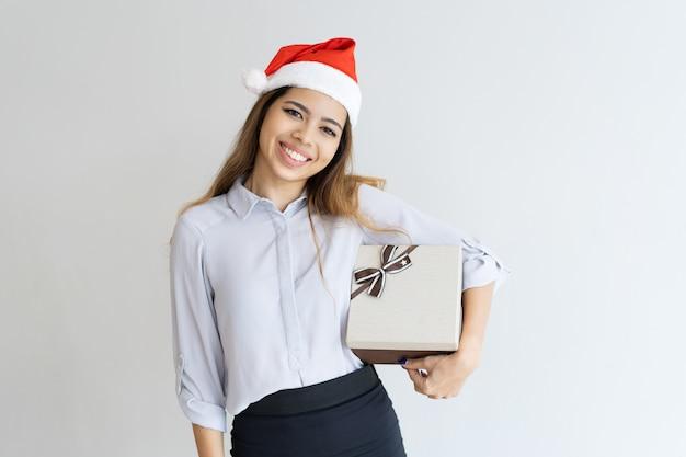 Heureuse jolie femme tenant une boîte-cadeau sous son aisselle Photo gratuit