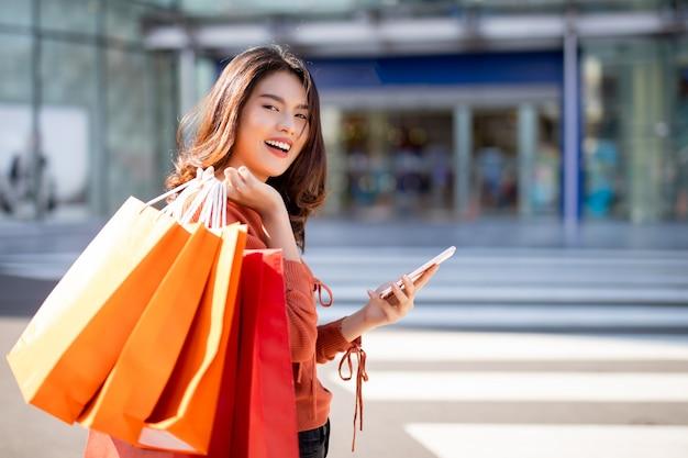 Heureuse jolie fille asiatique tenant des sacs à provisions lors de l'utilisation de smartphone Photo Premium