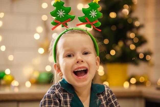 Heureuse Jolie Fille En Pyjama Prépare La Pâte Pour Les Cookies Du Nouvel An Pour Célébrer Noël. Photo Premium