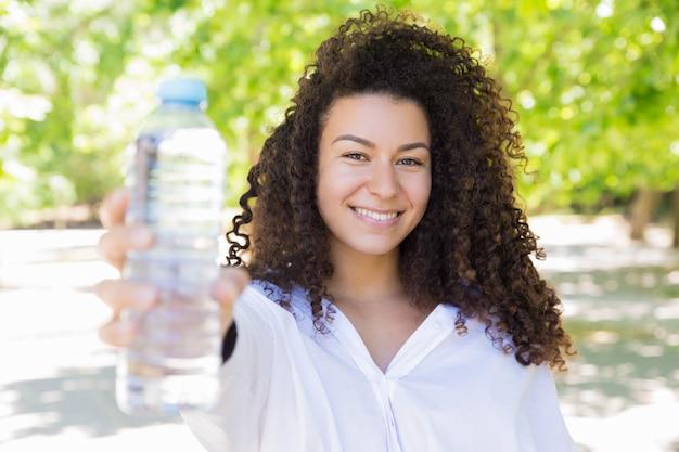 Heureuse jolie jeune femme montrant une bouteille d'eau dans le parc Photo gratuit