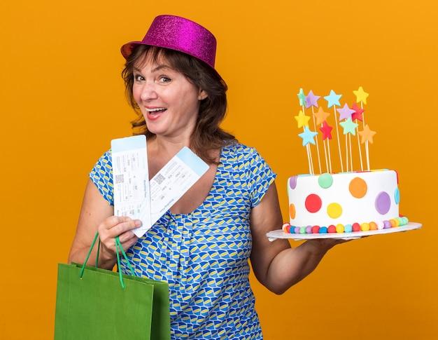 Heureuse Et Joyeuse Femme D'âge Moyen En Chapeau De Fête Tenant Un Sac En Papier Avec Des Cadeaux Tenant Un Gâteau D'anniversaire Et Des Billets D'avion Photo gratuit