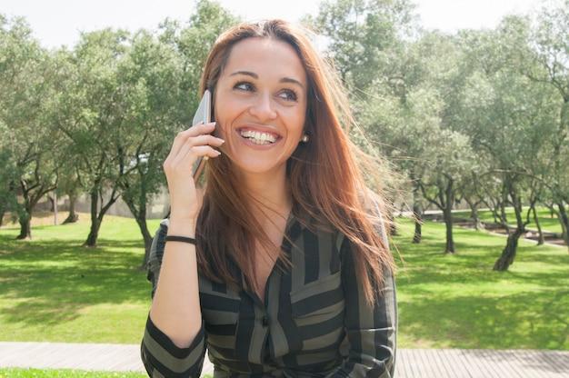 Heureuse joyeuse jeune femme discutant sur la cellule à l'extérieur Photo gratuit