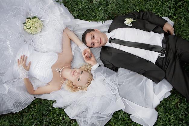 Heureuse mariée et le marié couché sur l'herbe verte Photo Premium