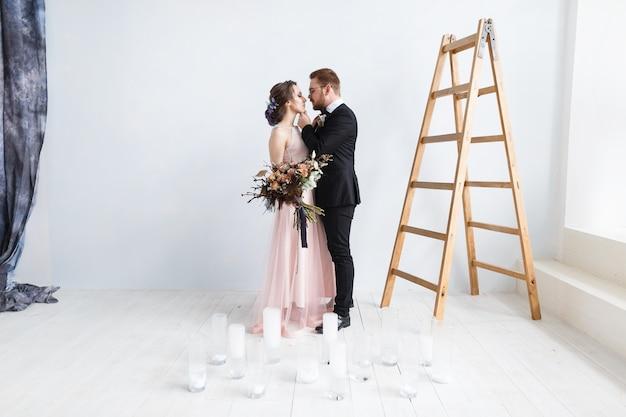 Heureuse mariée et le marié sur l'échelle au studio. fond de mur blanc isolé Photo gratuit