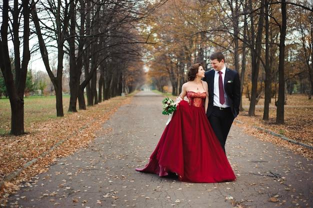 Heureuse mariée et le marié à pied dans la forêt d'automne. Photo Premium