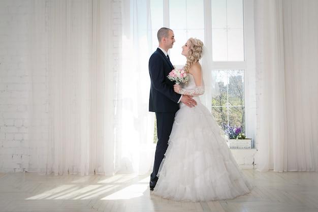 Heureuse mariée et le marié à la promenade de mariage devant la fenêtre Photo Premium