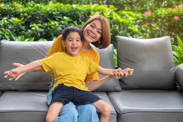 Heureuse mère asiatique et son fils rire assis à l'extérieur Photo Premium