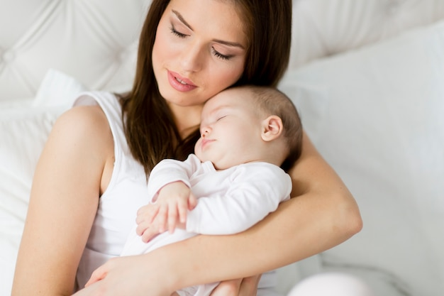 Heureuse mère avec bébé sur le lit Photo Premium