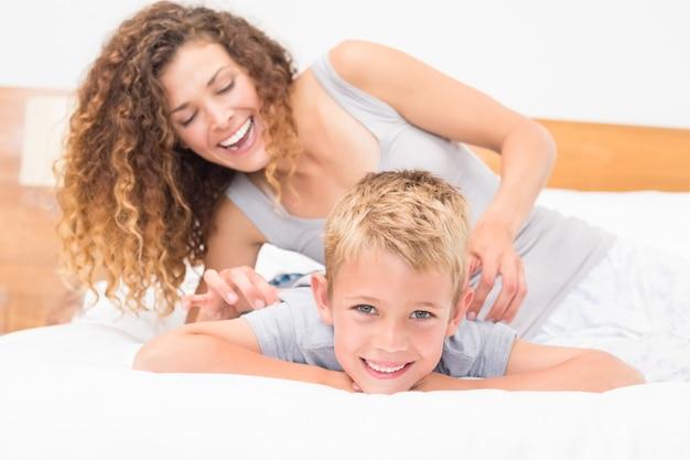 Heureuse mère chatouillant son fils mignon sur le lit Photo Premium