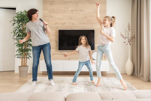 Heureuse Mère Et Deux Filles S'amusant à Chanter Une Chanson De Karaoké Dans Des Brosses à Cheveux. Photo Premium