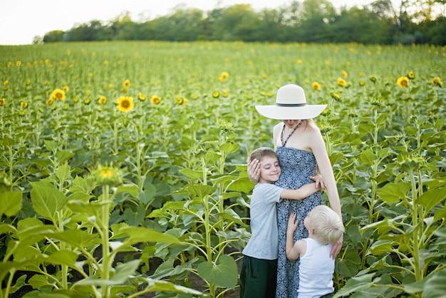 Heureuse mère enceinte embrassant deux petits fils Photo Premium