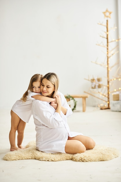 Heureuse mère enceinte et ses filles s'embrassent Photo Premium