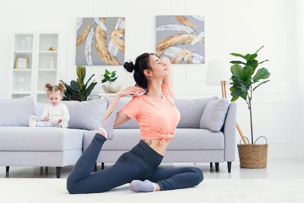 Heureuse Mère Faisant Des Exercices Du Matin Dans La Pose De Yoga Pendant Que Sa Petite Fille Joue à La Maison. Jeune Maman Adorable S'amusant à Pratiquer La Méditation Relaxante Le Week-end Sans Stress Avec Bébé. Photo Premium