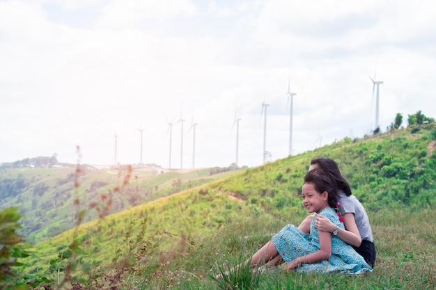 Heureuse Mère De Famille Asiatique Et Fille Assise Au Sommet D'une Montagne Magnifique Avec La Turbine En Arrière-plan Photo Premium
