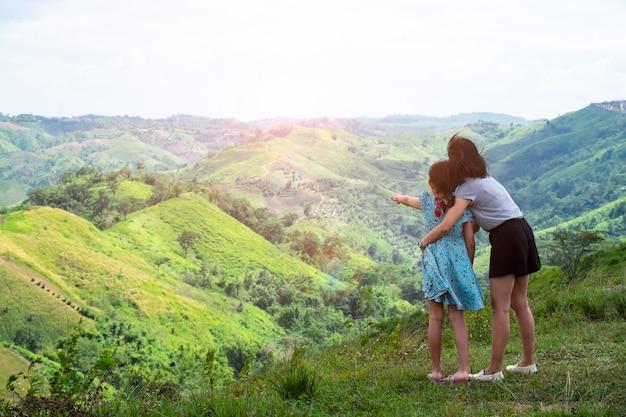 Heureuse Mère De Famille Asiatique Et Fille Debout Au Sommet De La Belle Montagne Tenant Mains Levées Photo Premium