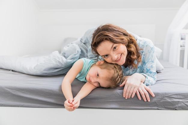 Heureuse mère et fille allongée sur le lit Photo gratuit