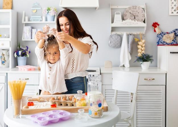 Heureuse mère et fille jouant avec de la farine Photo gratuit