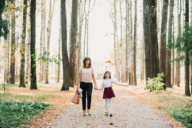 Heureuse mère et fille marchant dans le parc Photo Premium
