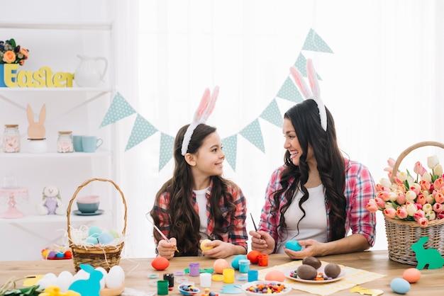 Heureuse mère et fille peignant les oeufs de pâques avec pinceau à la maison Photo gratuit