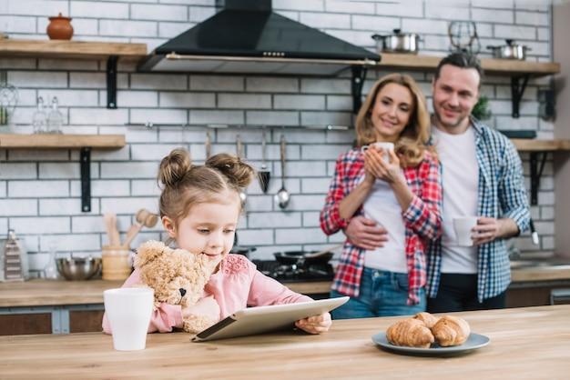 Heureuse mère et fille à la recherche de leur enfant à l'aide de tablette numérique dans la cuisine Photo gratuit