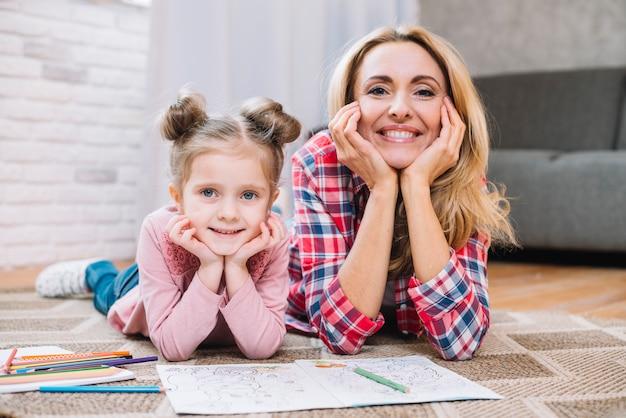 Heureuse mère et fille regardant la caméra dans le salon Photo gratuit