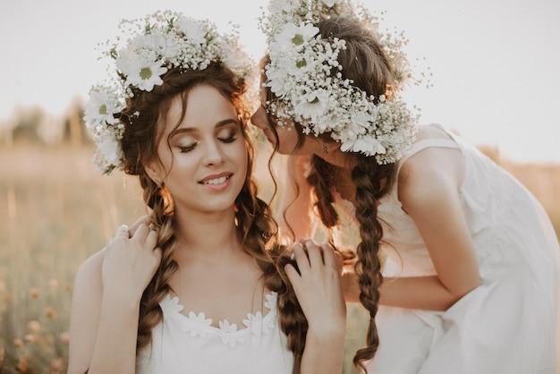 Heureuse Mère Et Fille Sourient Et S'enlacent Dans Le Domaine En été En Robes Blanches Avec Des Tresses Et Des Couronnes Florales Photo Premium