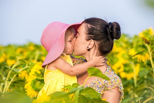 Heureuse Mère Avec La Fille Sur Le Terrain Avec Des Tournesols Photo Premium